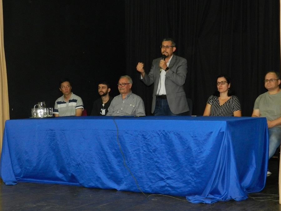 diretor geral de Pinheiral em pé e demais convidados sentdos à mesa de abertura
