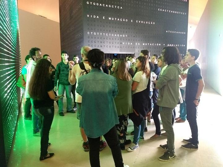 Grupo de alunos ouve orientação do guia dentro do museu do amanhã