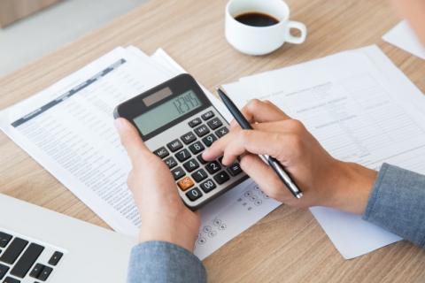 mãos segurando calculadora e caneta, sobre papeis e contas em uma mesa