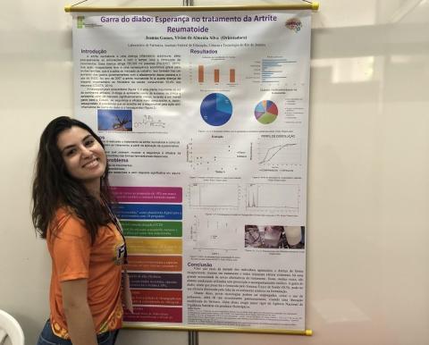 aluna Joanna Gomes posando para foto com o banner de seu projeto na FENECIT