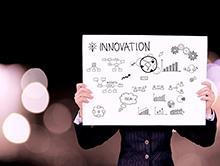 """Vemos uma pessoa segurando um cartaz em que se lê """"Innovation"""" e vários desenhos esquemáticos"""