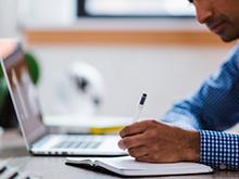 Vemos um homem estudando ao computador e tomando notas em um caderno