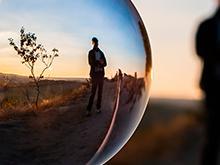 Vemos uma bola de vidro que reflete a imagem de um homem em um campo aberto, com um pequeno arbusto ao lado sob o pôr do sol