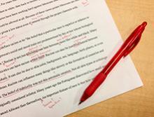 Vemos um texto impresso escrito na língua inglesa com correções em vermelho feitas pela caneta que se encontra deitada na lateral direita do papel